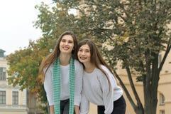 Duas amigas estão rindo felizmente, abraçando-se Fotografia de Stock Royalty Free