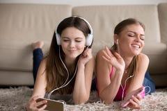 Duas amigas felizes nos fones de ouvido que apreciam sua música favorita fotos de stock