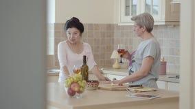 Duas amigas maduras encontraram-se e posição de conversa na cozinha a menina Preto-de cabelo gesticula e diz algo a filme