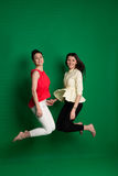 Duas amigas morenos que levantam no fundo verde Foto de Stock Royalty Free