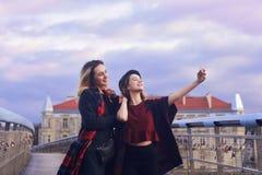Duas amigas novas bonitas do estudante que têm o divertimento que faz as caras engraçadas e que toma auto-retratos com Smart-tele fotos de stock royalty free