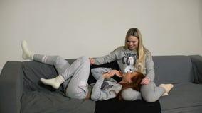 Duas amigas novas com o smartphone no sofá na casa vídeos de arquivo