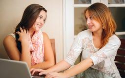 Duas amigas novas que falam na frente do computador fotografia de stock royalty free