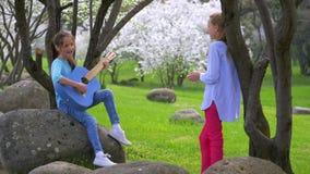 Duas amigas pequenas alegres que jogam a música na mola da guitarra no parque cena idílico bonita na natureza vídeos de arquivo