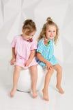 Duas amigas pequenas nos vestidos idênticos das cores diferentes que sentam-se em uma cadeira em um estúdio com paredes brancas Fotografia de Stock Royalty Free
