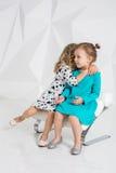 Duas amigas pequenas nos vestidos idênticos das cores diferentes que sentam-se em uma cadeira em um estúdio com paredes brancas Imagens de Stock Royalty Free
