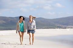 Duas amigas que andam e que falam na praia Imagens de Stock Royalty Free