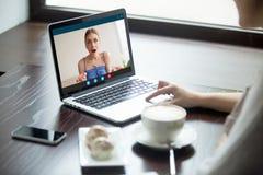 Duas amigas que conversam no portátil através da aplicação video da chamada imagens de stock