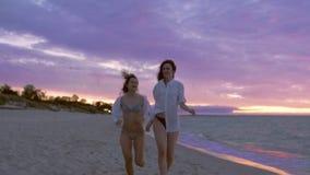 Duas amigas que correm ao longo da praia video estoque