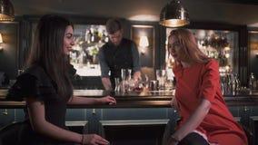 Duas amigas que sentam-se perto do contador da barra que tem fim interessante da conversação acima Barman na fatura do fundo filme