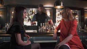 Duas amigas que sentam-se perto do contador da barra que tem fim interessante da conversação acima O barman dá-lhes cocktail vídeos de arquivo