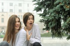 Duas amigas riem com a surpresa, vendo algo divertir-se Fotografia de Stock