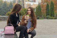 Duas amigas tentam aquecer-se com uma bebida quente no ar livre Imagem de Stock Royalty Free