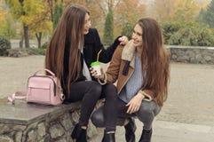 Duas amigas tentam aquecer-se com uma bebida quente no ar livre Fotos de Stock Royalty Free