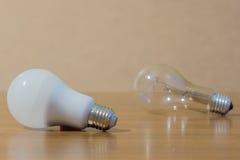 Duas ampolas Lâmpada branca e ordinária do diodo emissor de luz no fundo de madeira fotografia de stock