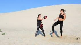 Duas atléticas, jovens mulheres em ternos pretos da aptidão são contratadas em um par, dão certo pontapés, em uma praia abandonad video estoque
