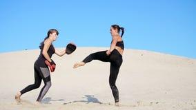 Duas atléticas, jovens mulheres em ternos pretos da aptidão são contratadas em um par, dão certo pontapés, trem para lutar, no ab video estoque