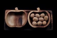 Duas bacias de madeira em um fundo preto com nozes imagens de stock royalty free