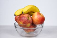 Duas bananas e quatro maçãs na bacia de vidro isolaram a composição no fundo branco imagem de stock