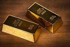 Duas barras de ouro no fundo de madeira imagem de stock