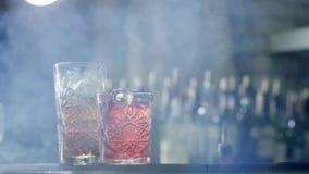 Duas bebidas alcoólicas refrigerando com gelo estão de lado a lado no fumo em fundo unfocused filme