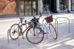 Duas bicicletas são estacionadas em um estacionamento especial da bicicleta em uma cidade inglesa pequena imagens de stock royalty free