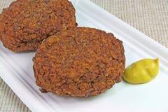 Duas bolas de carne com mostarda em uma placa de papel Imagem de Stock Royalty Free