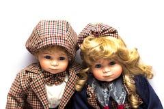 Duas bonecas cerâmicas dos jardineiro que sentam-se no fundo branco imagem de stock royalty free