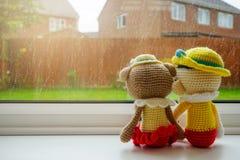 Duas bonecas de confecção de malhas menina e menino que guardam a mão que senta-se ao lado da janela imagem de stock