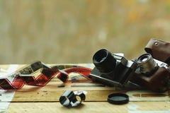 Duas câmeras da foto do vintage da velha escola e filmes dispersados na luz - tabela marrom Um no suporte de couro retro marrom d fotos de stock