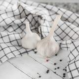 Duas cabeças brancas da mentira do alho em um fundo branco de madeira Encontram-se próximo uma toalha e os grãos de pimenta dispe imagem de stock