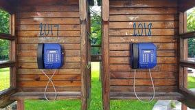 Duas cabines de telefone de madeira com telefones de pagamento O conceito pelo ano novo a 2018 Foto de Stock Royalty Free