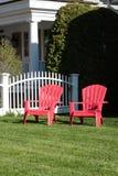 Duas cadeiras de gramado vermelhas vazias Foto de Stock Royalty Free