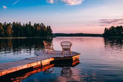 Duas cadeiras de madeira em um cais de madeira que negligencia um lago no por do sol Fotos de Stock Royalty Free