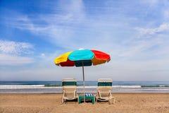 Duas cadeiras de praia e um guarda-chuva colorido ao longo da linha costeira foto de stock royalty free