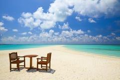 Duas cadeiras e uma tabela estão na praia Fotografia de Stock