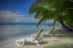 Duas cadeiras lounging na praia Fotografia de Stock Royalty Free