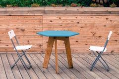 Duas cadeiras modernas brancas vazias com a tabela azul no assoalho de madeira do teatro Fotos de Stock