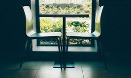 Duas cadeiras modernas do estilo perto da tabela pequena bonito perto da janela com o tiro interior preto e branco da parede de t Imagem de Stock