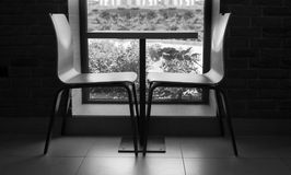 Duas cadeiras modernas do estilo perto da tabela pequena bonito perto do vento Fotografia de Stock