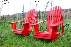 Duas cadeiras vermelhas no campo Fotos de Stock Royalty Free