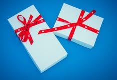 Duas caixas de presente brancas no fundo azul Fotos de Stock