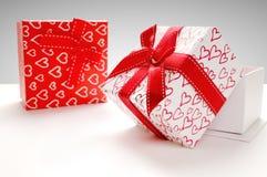 Duas caixas de presente com os corações impressos com fundo cinzento Fotos de Stock