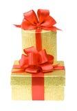 Duas caixas de presente do ouro com fitas vermelhas Fotografia de Stock Royalty Free