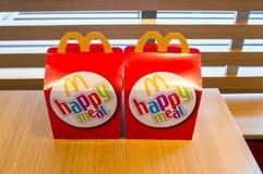 Duas caixas felizes da refeição de Mcdonalds na tabela de madeira Fotos de Stock