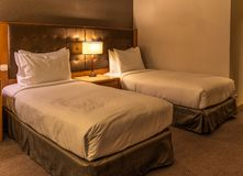 Duas camas e cabeceira comum com candeeiro de mesa em uma sala de hotel padrão fotos de stock royalty free
