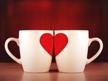 Duas canecas com a imagem de um coração meio Imagens de Stock Royalty Free