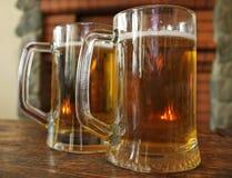 Duas canecas de cerveja em uma tabela de madeira Fotos de Stock Royalty Free