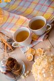 Duas canecas de chá quente em um guardanapo amarelo de linho Hortênsia secada, limão, castanha, canela fotografia de stock royalty free