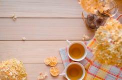 Duas canecas de chá quente em um guardanapo amarelo de linho Hortênsia secada, limão, castanha, canela Lugar para a inscrição foto de stock royalty free